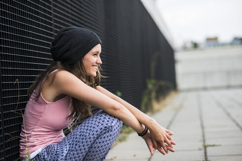 Laughing teenage girl with wool cap crouching in front of a black facade - UUF001636
