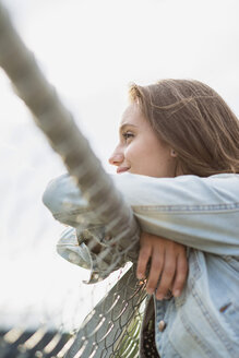 Profile of smiling teenage girl wearing jeans jacket leaning on a fence - UUF001613