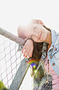 Portrait of smiling teenage girl leaning on a fence - UUF001614