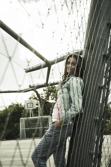 Smiling teenage girl standing behind a wire fence on sports field - UUF001641