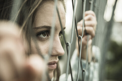 Teenage girl looking through a wire fence - UUF001642