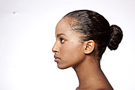 Profile of young woman with bun in front of white background - KDF000491