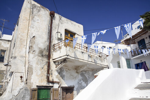 Greece, Cyclades, Naxos, Old house and Greek pennants on a line - KRPF000837