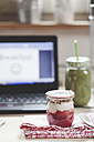 Green smoothie and yogurt breakfast on desk with laptop - SBDF001179