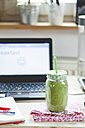 Green smoothie on desk with laptop - SBDF001200
