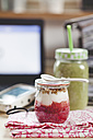 Green smoothie and yogurt breakfast on desk with laptop - SBDF001181