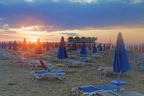 Italy, Friuli-Venezia Giulia, Province of Udine, Lignano Sabbiadoro, Beach with sun loungers in the evening, Terrazza a Mare in the background - GFF000536