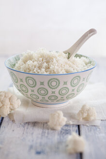 Bowl of cauliflower rice and cauliflower florets on cloth and wood - SBDF001226