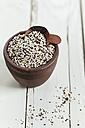 Earthenware dish of organic quinoa, Chenopodium quinoa, on white wood - SBDF001160