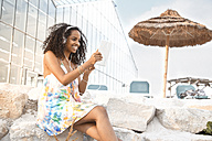 Happy young woman with headphones and digital tablet outdoors - KD000395