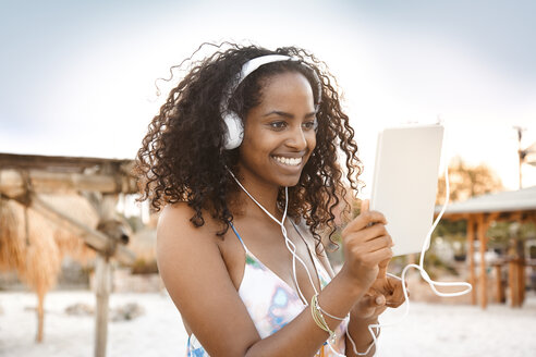 Happy young woman with headphones and digital tablet outdoors - KD000398