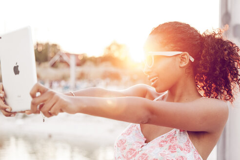 Young woman taking selfie with digital tablet at sunset - KD000416