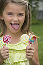 Portrait of girl holding lollipops - YFF000215