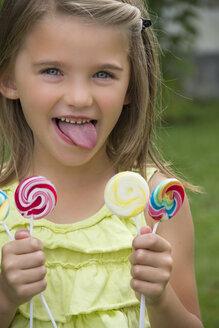 Portrait of girl holding lollipops - YFF000215