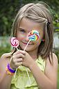 Portrait of girl holding lollipops - YFF000217