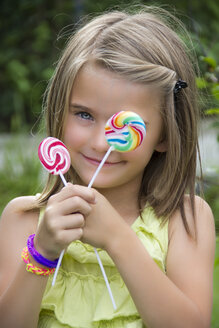 Portrait of girl holding lollipops - YFF000217