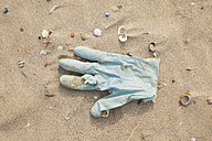 Belgium, rubber glove lying on sandy beach at North Sea coast - GWF003126