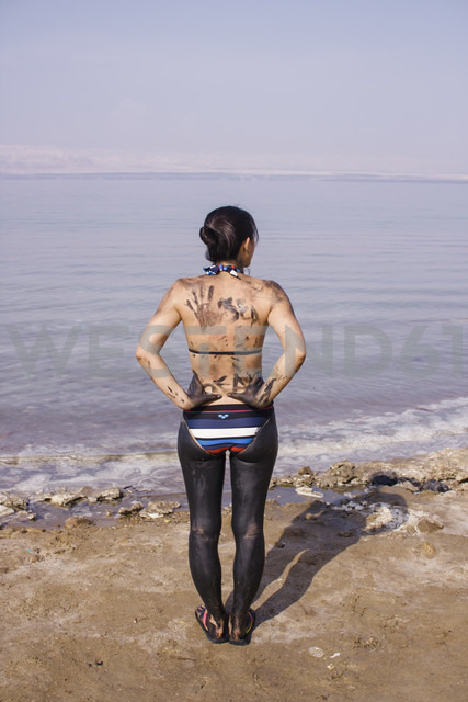 Jordan, Japanese woman with dead sea mud on her lower body at a beach on the Jordanian side of the dead sea - FLF000498