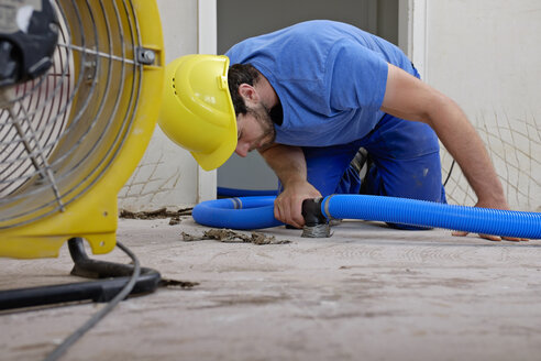 Worker fixing hose of dehumidifier in an apartment which is damaged by flooding - LAF001027