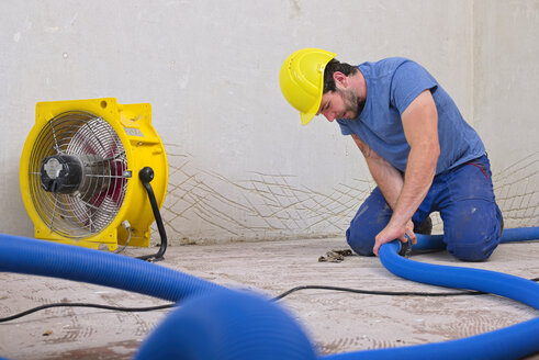 Worker fixing hose of dehumidifier in an apartment which is damaged by flooding - LAF001028