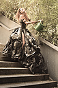Woman wearing dress made from bin bags watering flowers - FCF000414