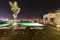 Morocco, Fes, view to lighted swimming pool at roof terrace of a hotel by night - KM001385