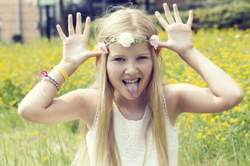 Portrait of a girl sitting on a meadow making a face - GDF000388