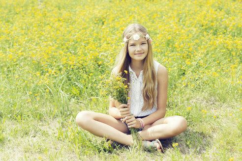 Portrait of a smiling girl sitting on a flower meadow wearing flowers - GDF000373
