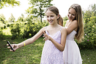Girl taking a selfie while her sister brushing her hair - GDF000377