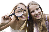 Portrait of two smiling girls with magnifying glass - GDF000383