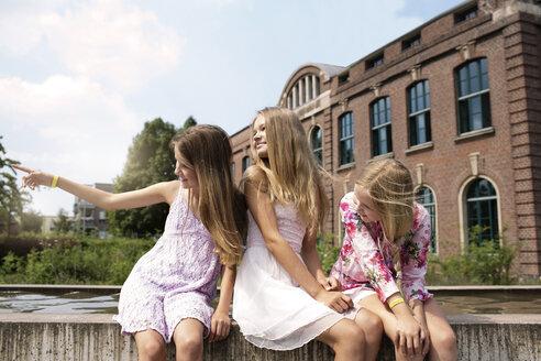 Three girls sitting on a wall watching something - GDF000381