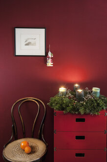 Advent wreath on sideboard at red wall - HHF004844