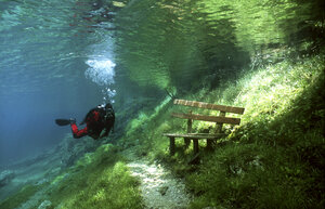 Austria, Styria, Tragoess, lake Gruener See, diver in front of a park bench - YRF000049