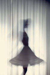 Silhouette of a young woman dancing in front of a white curtain - BRF000577