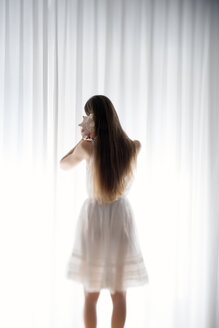 Young woman standing with a shell in front of a white curtain, back view - BRF000574