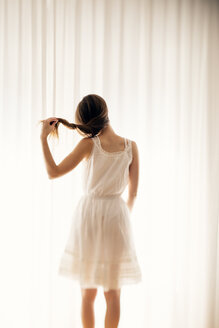 Young woman playing with her hair in front of a white curtain, back view - BRF000578