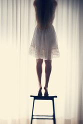 Young woman standing on a stool in front of a white curtain, back view - BRF000579