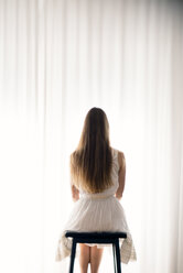 Young woman sitting on a stool in front of a white curtain, back view - BRF000582