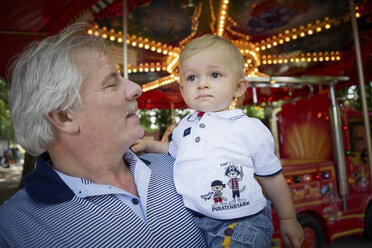 Germany, Oberhausen, Granfather and grandson in front of carousel - GDF000396