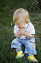 Germany, Oberhausen, Blond baby boy sitting on grass in park - GDF000398