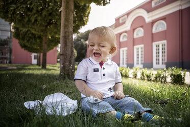 Germany, Oberhausen, Blond baby boy sitting in park of Oberhausen Castle - GDF000401