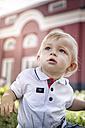 Germany, Oberhausen, Blond baby boy sitting in park of Oberhausen Castle - GDF000402