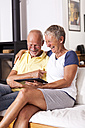 Senior couple sitting on couch having fun with digital tablet - JUNF000002