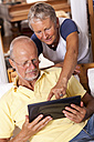 Senior couple at home using digital tablet - JUNF000012