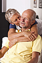 Senior woman hugging and kissing her husband - JUNF000013