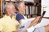 Senior couple sitting on couch with newspaper using digital tablet - JUNF000009