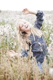 Portrait of smiling girl having fun in a field - MAE009018