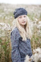 Portrait of girl standing in a field wearing headgear and shirt with floral pattern - MAE009020