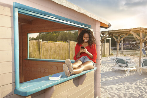 Laughing young woman with smartphone at city beach - KD000498