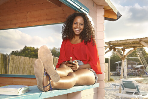 Smiling young woman with smartphone at city beach - KD000499